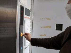 綿棒でエレベーターのボタンを押す