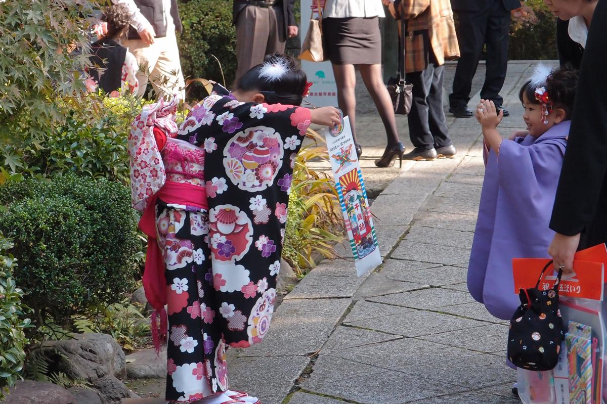 カメラに千歳飴を向ける七五三の女の子