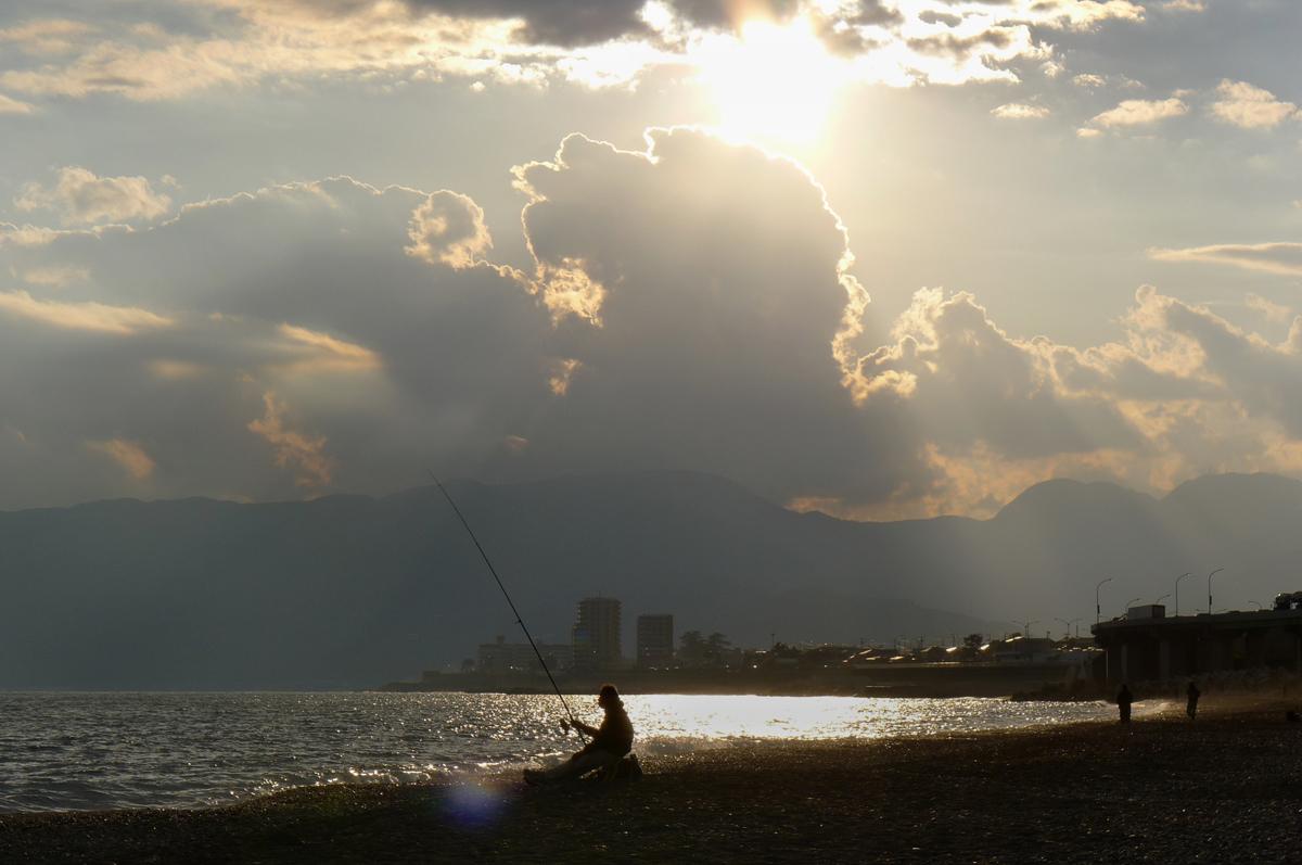 傾き始めた日の下で国府津海岸の釣り人