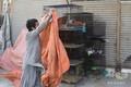 パキスタンで閉鎖されたペットショップの外におかれた動物の檻を覆う店員 - コピー